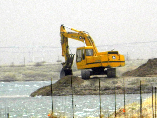 Excavator Opening a Channel Between Ponds