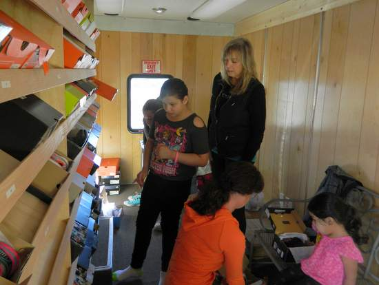 Karen Voepel Helps a Student Select a Pair of Shoes from the Shoe Cruizer