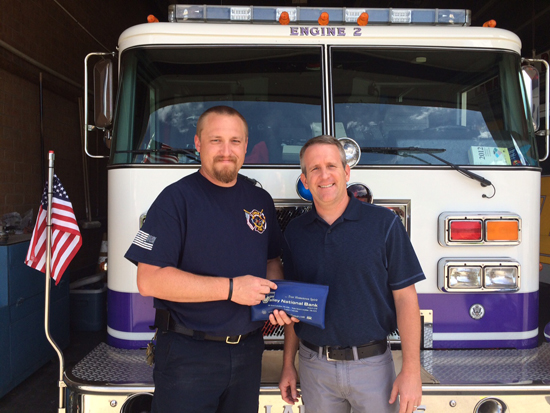 Library Interim Director, Todd Schaefer gives the money raised to Fire Chief, Jeremy Burkhart